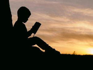 man reading with bible during sunset- worrying verses in the bible